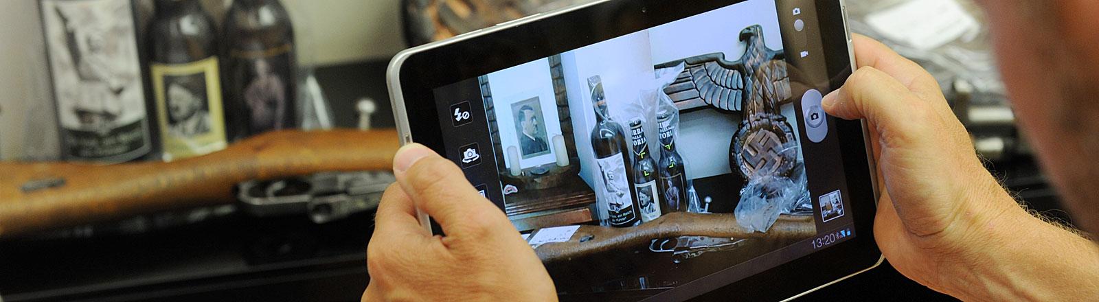 Ein Journalist fotografiert mit einem Tablet-PC beschlagnahmte Waffen, Propagandamaterial und Nazi-Devotionalien.
