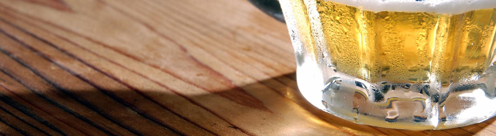 Ein halbvoller Bierkrug auf einem Tisch