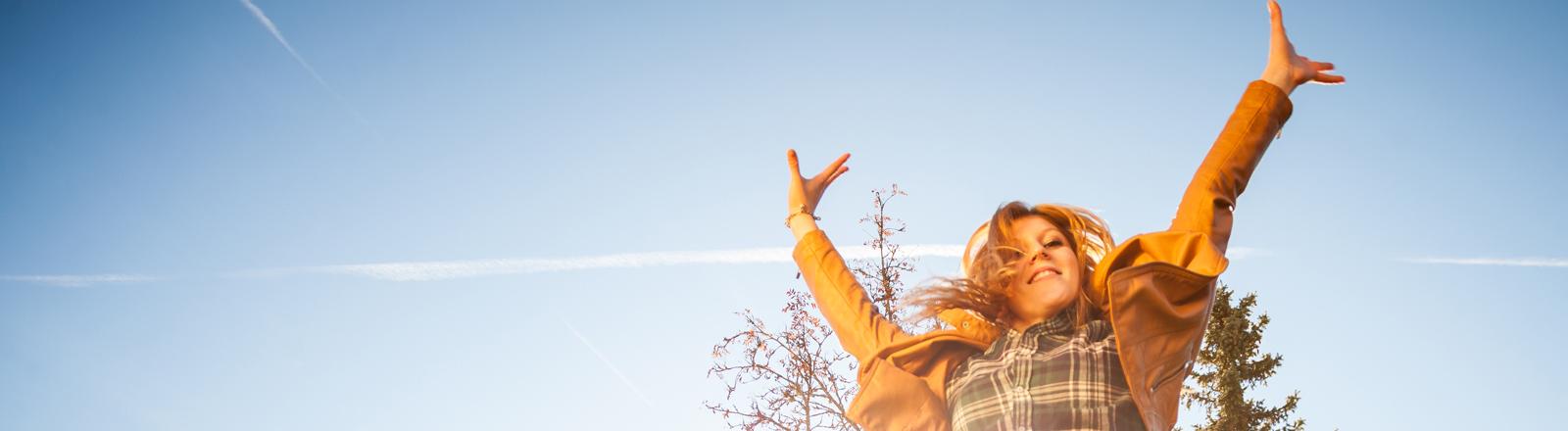 Eine junge Frau springt in die Luft