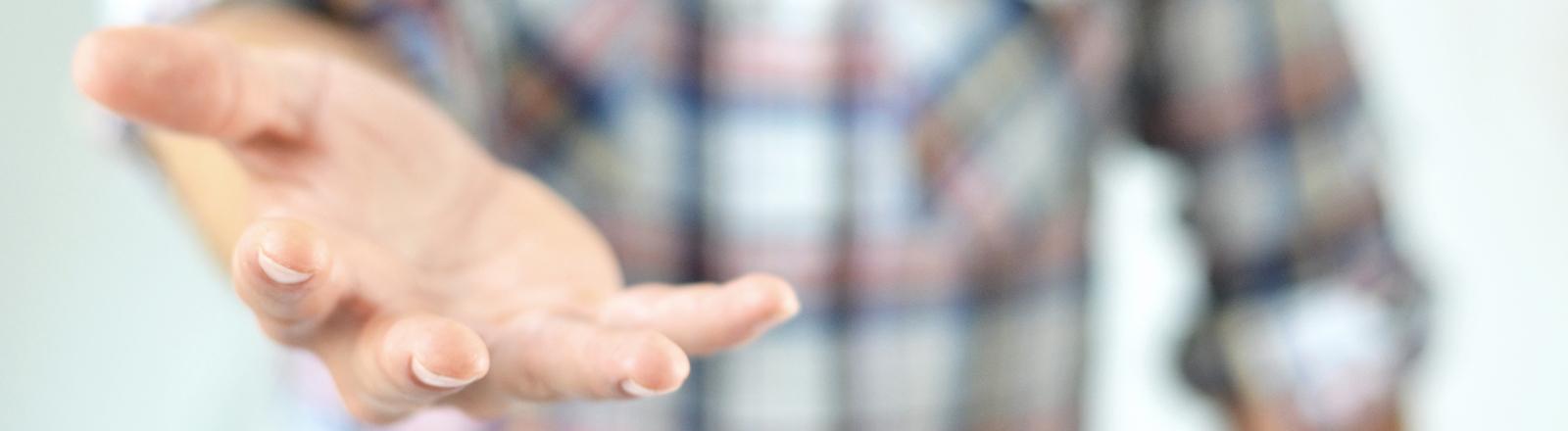 Ein Mann hält die Hand auf