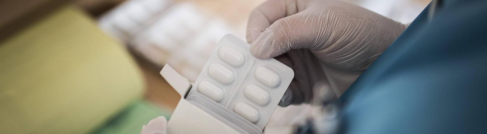 Eine Pflegekraft holt Tabletten aus einer Verpackung
