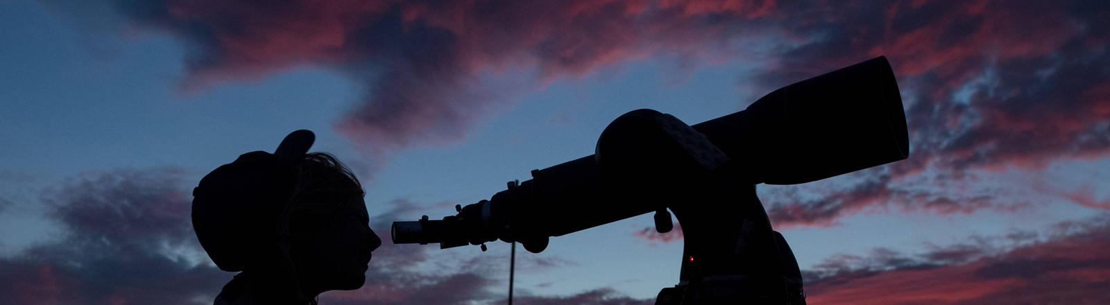 Eine Frau schaut durch ein Teleskop