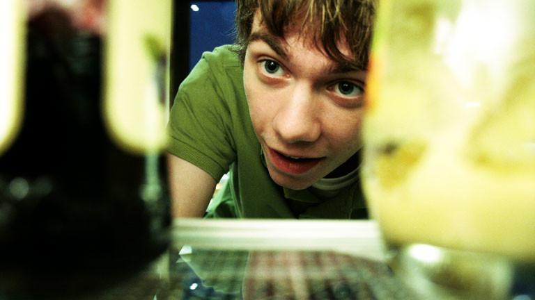 Ein junger Mann schaut in den Kühlschrank.