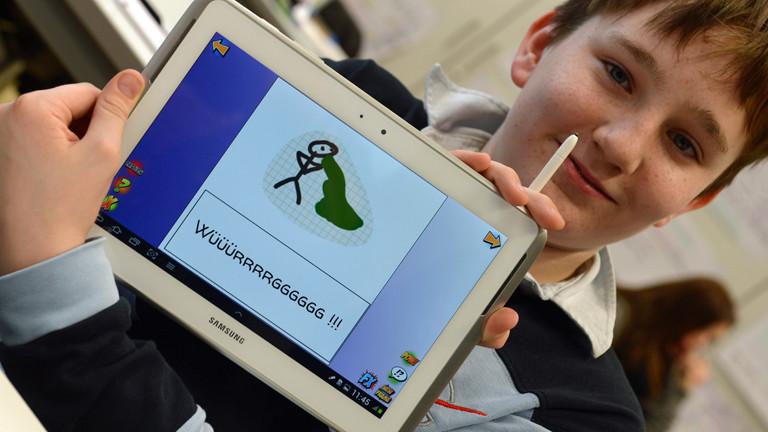 Der Schüler Max zeigt eine von ihm gefertigte Zeichnung auf einem Tablet-PC: ein kotzendes Strichmännchen.