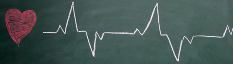 Ein Herz und Herzrhythmuslinien auf einer Tafel gezeichnet