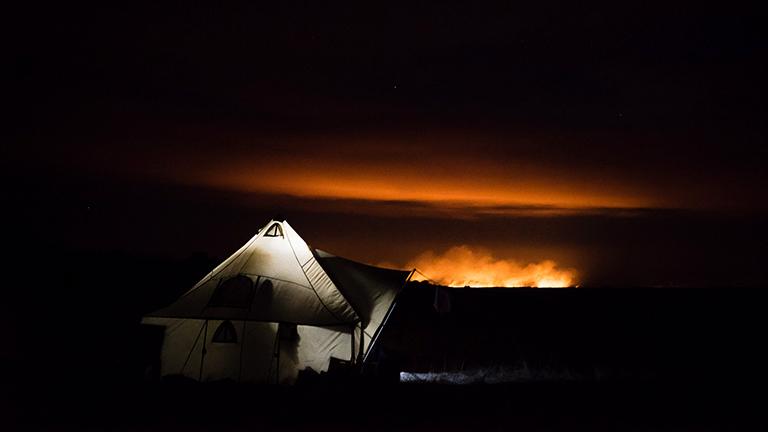 Ein Steppenfeuer in der mongolischen Steppe bei Nacht in der Nähe eines Zeltcamps