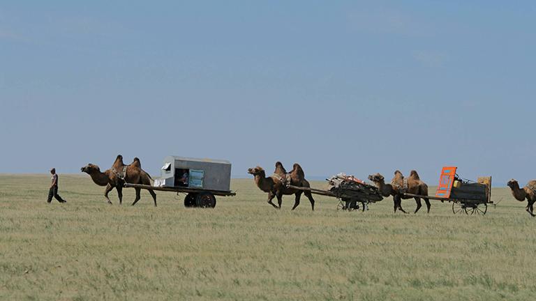Nomaden wandern mit Kamelkarren durch die mongolische Steppe