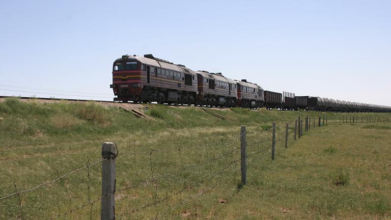 Eingezäunte Zugschienen laufen durch die mongolische Steppe