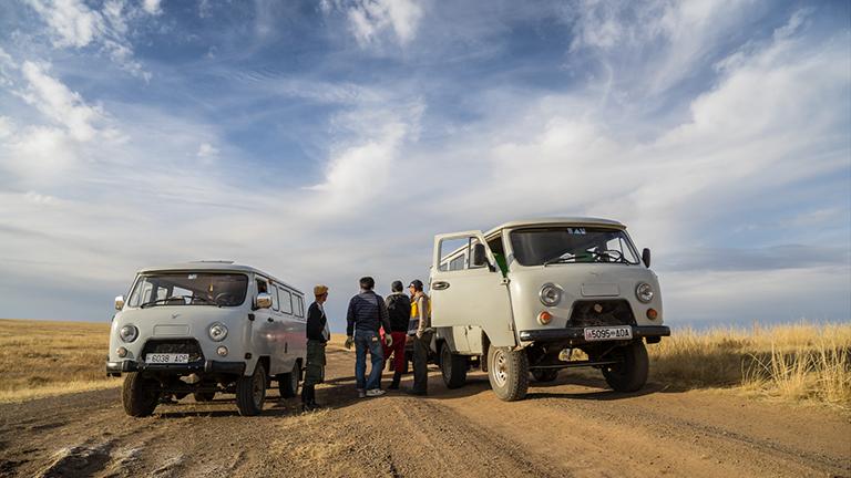 Zwei alte Lastwagen stehen in der mongolischen Steppe, daneben eine Gruppe von Menschen