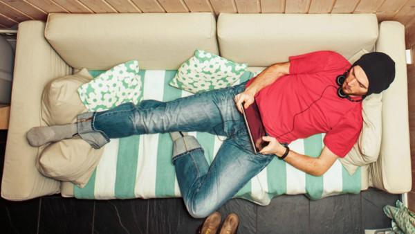 Ein Mann liegt faul auf der Couch und dödelt mit seinem Tablet.