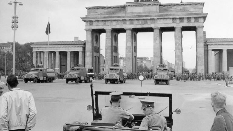 1961: Ein Jeep der britischen Militärpolizei auf dem Platz vor dem Brandenburger Tor, im Hintergrund Wasserwerfer und Volkspolizei.