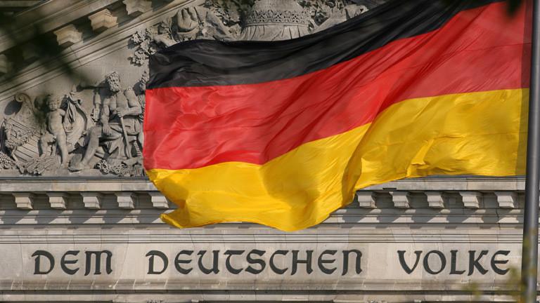"""Reichtsgasgebäude mit einer deutschen Flagge davor und der Aufschrift """"Dem Deutschen Volke""""."""