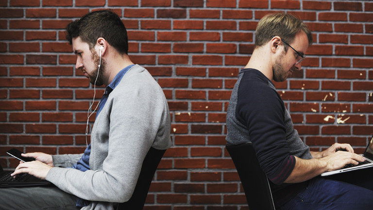Zwei Männer sitzen mit Laptop Rücken an Rücken.