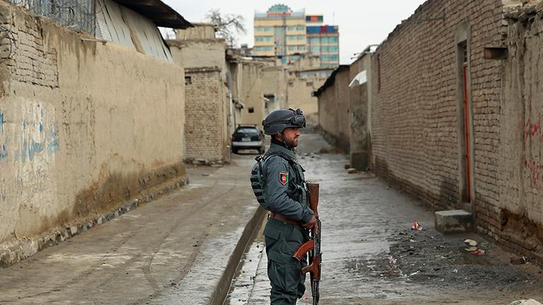 Ein afghanischer Soldat steht in einem zerstörten Viertel