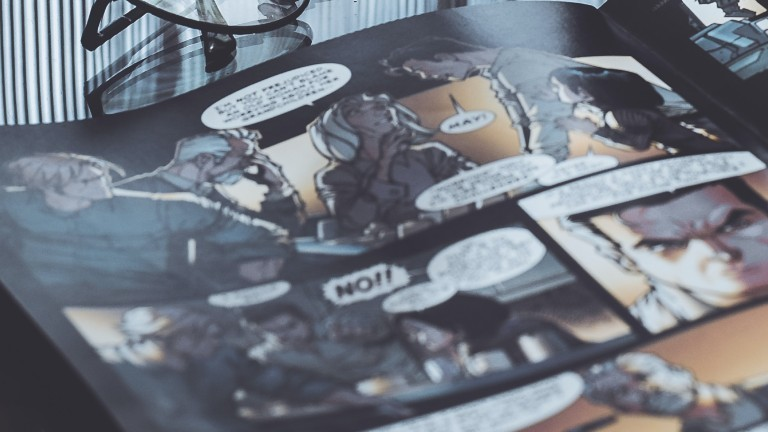 Ein Comicheft liegt aufgeschlagen auf einem Tisch.