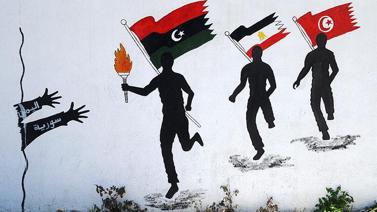"""Arabische Flaggenläufer mit der """"Flamme der Freiheit"""": in der Reihenfolge der Revolutionen rennen Tunesien, Ägypten und vorne Libyen mit der Flamme auf sich entgegen streckende Hände zu."""