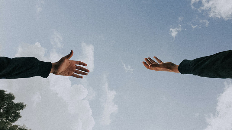 Zwei Hände werden zueinander ausgestreckt, dahinter blauer Himmel mit Wolken.