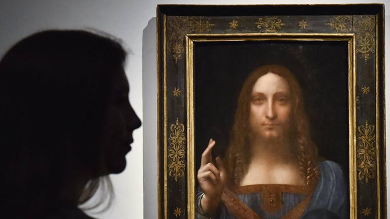"""Eine Mitarbeiterin von Christie's in London betrachtet Leonardo da Vincis Gemälde """"Salvator Mundi""""."""