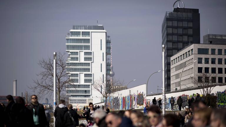 Touristen an einem Mauersegment der Berliner Mauer an der ehemaligen innerdeutschen Berliner Grenze am Mauerstreifen an der East-Side-Gallery in Berlin Kreuzberg-Friedrichshain.