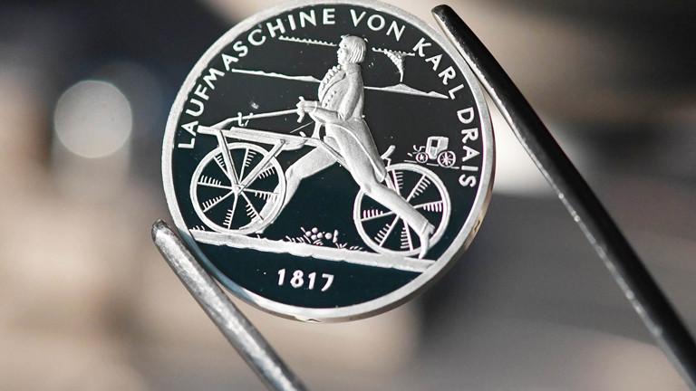 Eine Münze zeigt eine Laufmaschine