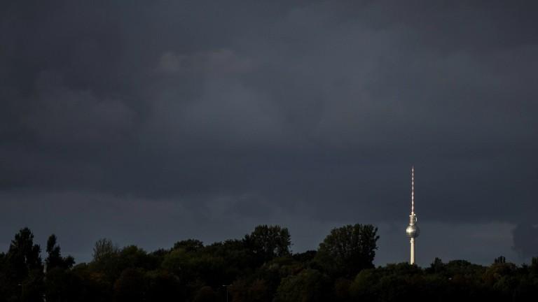 Der Fernsehturm in Berlin zeichnet sich vor dunklen Regenwolken ab.