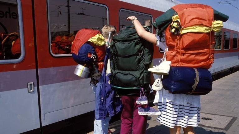 Menschen mit Reiserucksäcken am Bahnhof