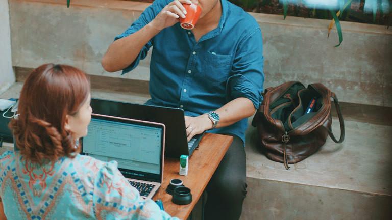 Zwei Personen sitzen sich gegenüber in einem Café vor ihren Laptops.