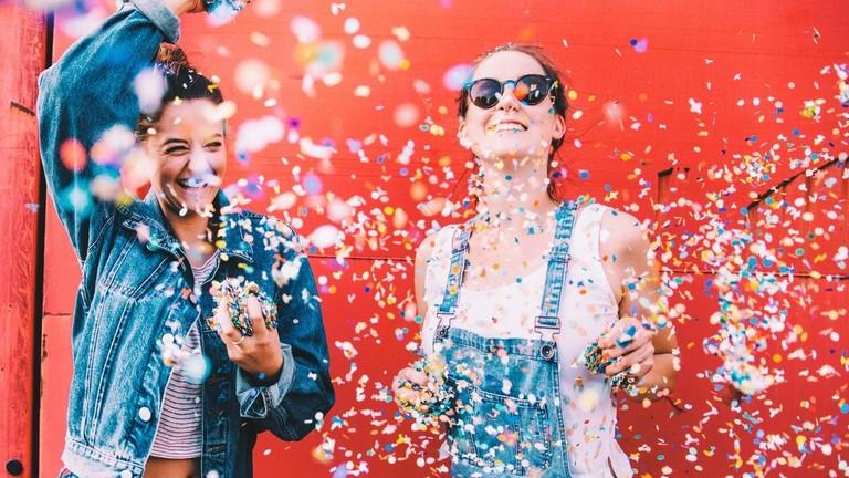 Zwei Frauen tanzen und schmeißen Konfetti