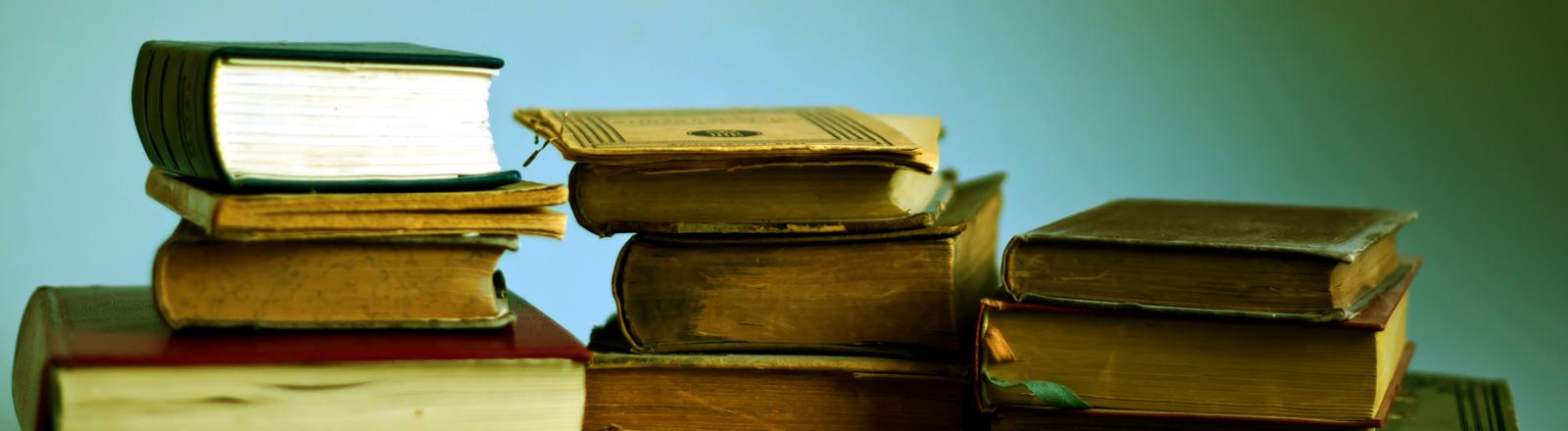 Drei Stapel alter Bücher