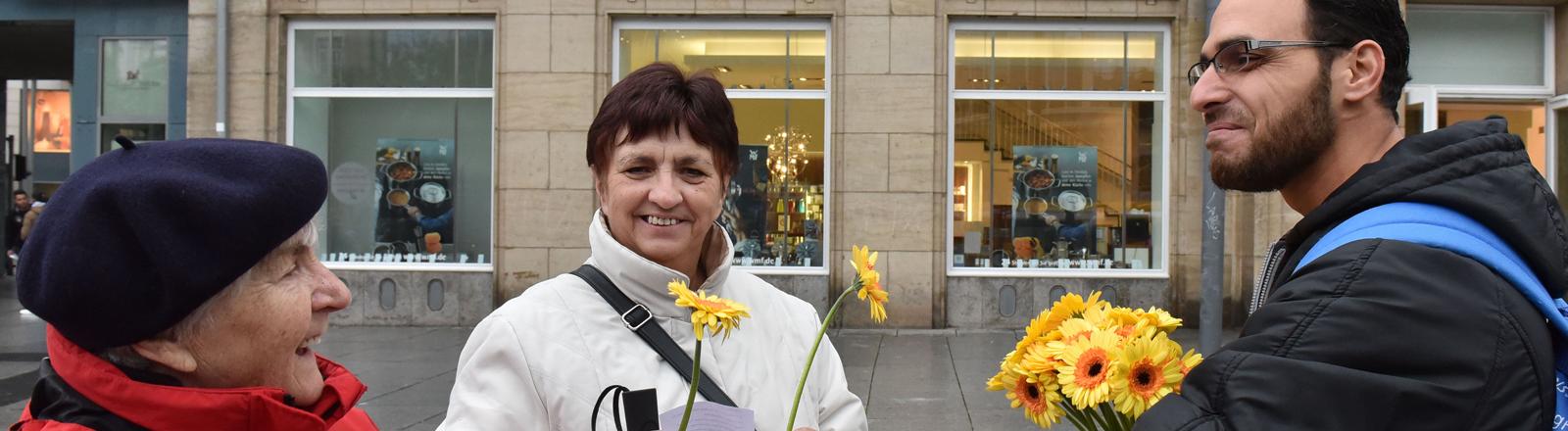Ein junger Mann überreicht zwei älteren Damen Blumen als Dankeschön