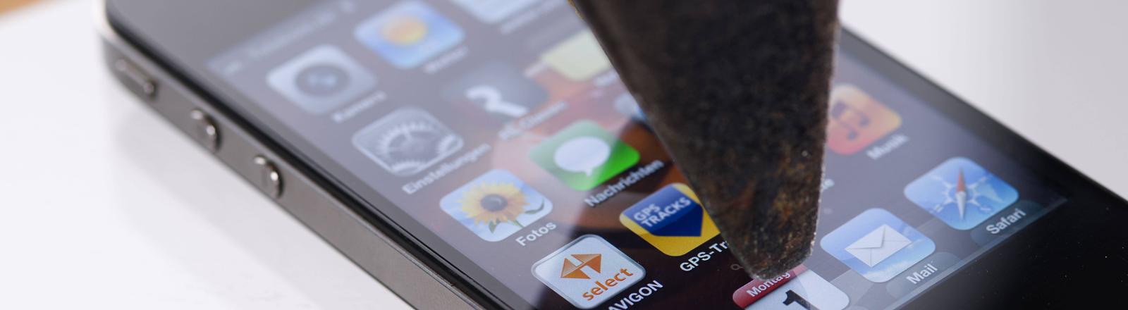 Ein Hammer wird auf ein iPhone geschlagen