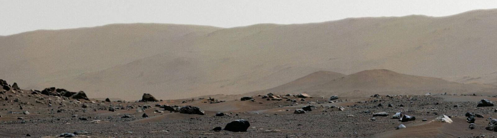 Eine Landschaft auf dem Mars. Im Vordergrund liegen Steine und Geröll. Im Hintergrund sandige Hügel und ein Streifen Himmel.