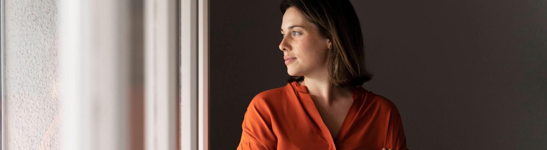 Junge Frau schaut nachdenklich aus dem Fenster.