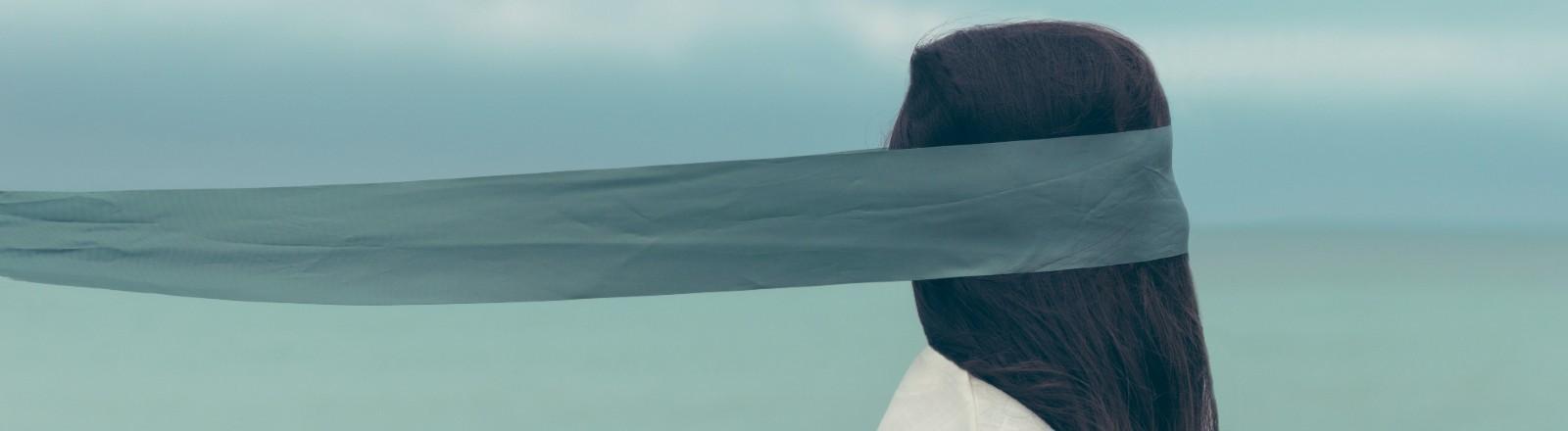 Frau mit Augenbinde am Strand.
