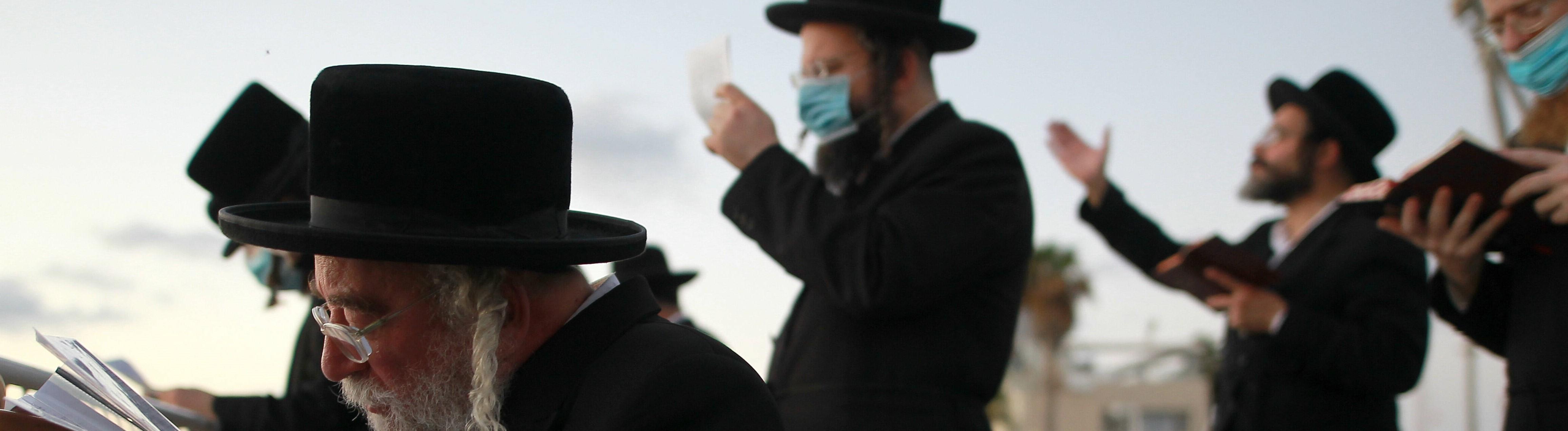 Eine Gruppe ultraorthodoxer jüdischer Männer betet. Einige von ihnen tragen einen Mundschutz.