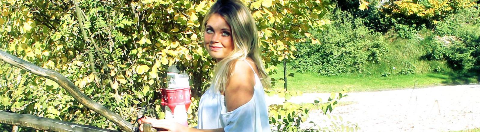 Junge blonde Frau in einem Park