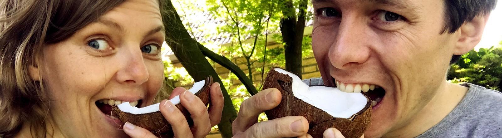 Matthias Nienhaus und seine Schwester Andrea essen eine Kokosnuss