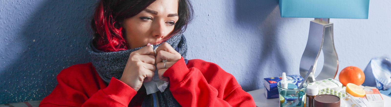 Frau liegt mit Schal, dickem Pulli und Taschentüchern im Bett