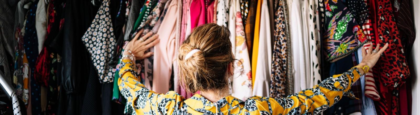 Frau steht vor einem vollen Kleiderschrank.