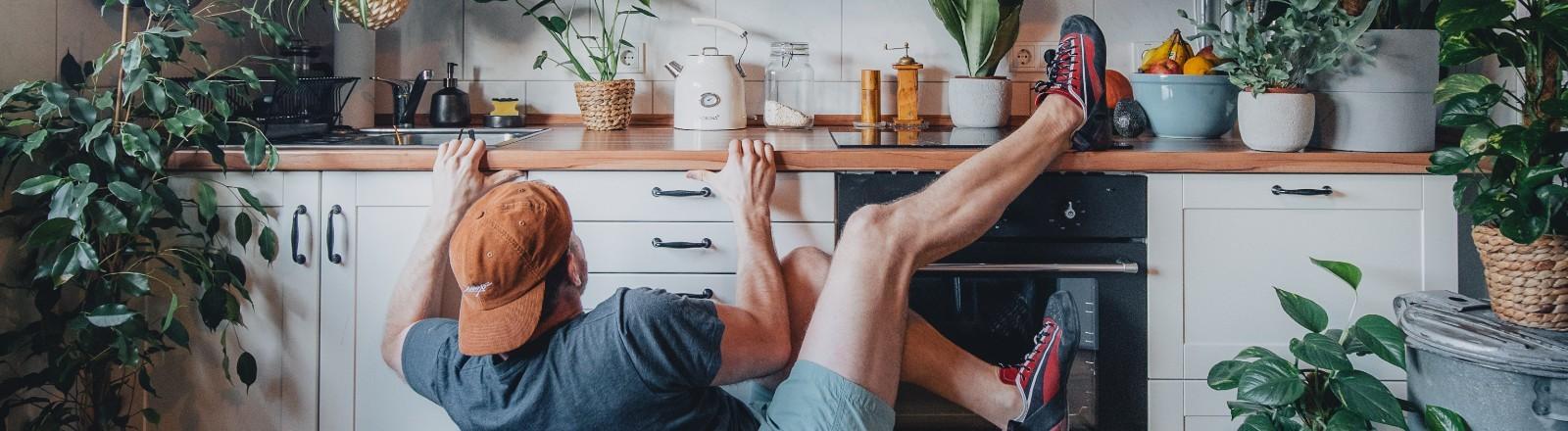 Ein Mann bouldert in seiner Küche