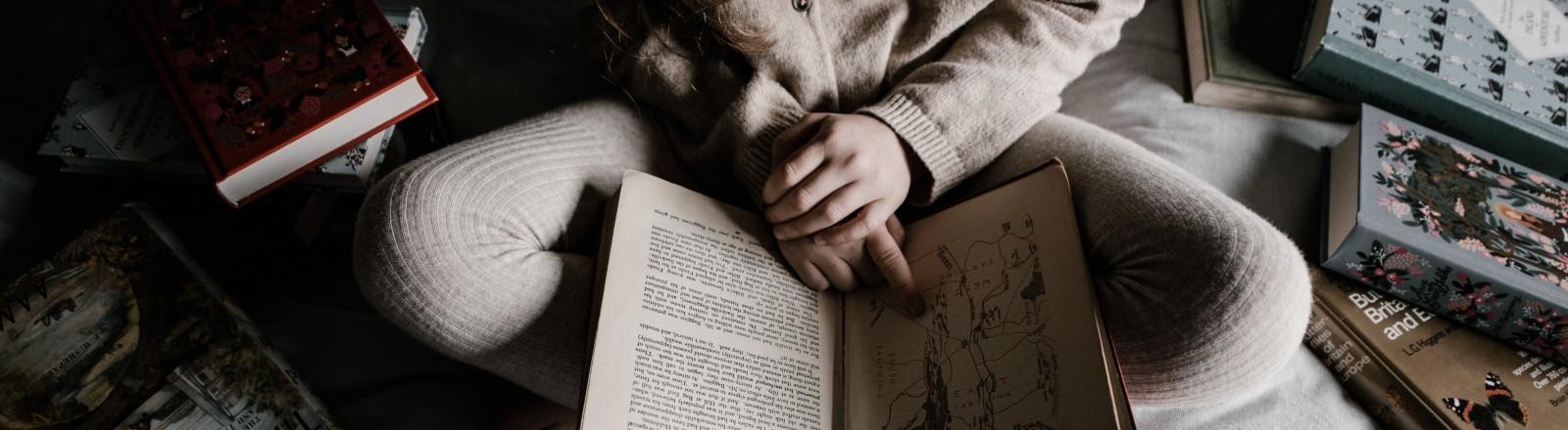 Ein Mädchen liest Bücher im Bett