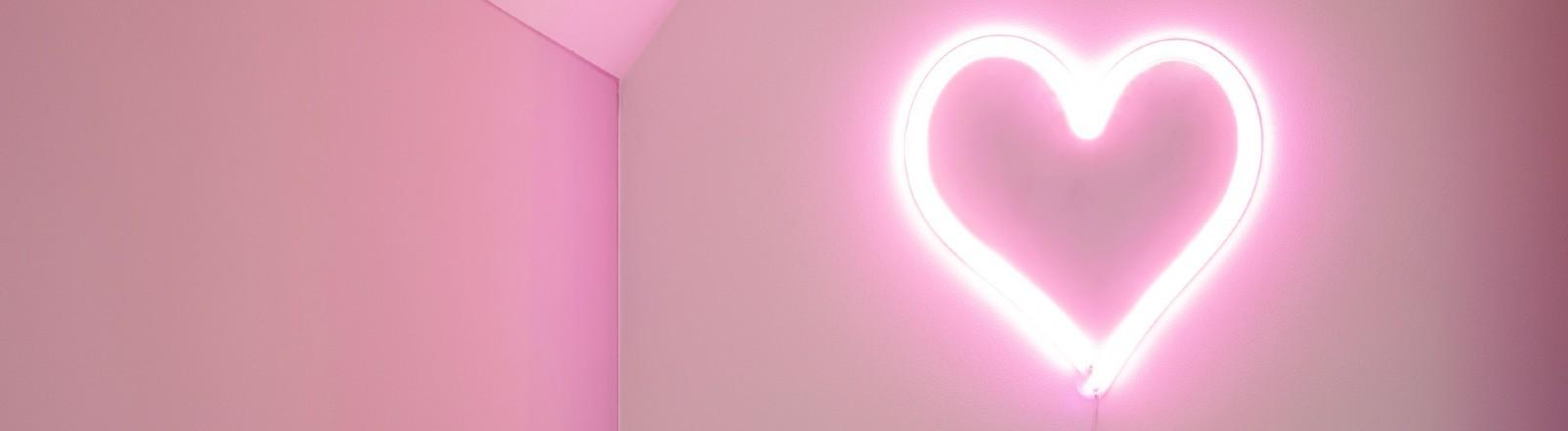 Leuchtendes Neonherz auf rosa Wänden.