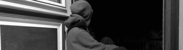 Person von hinten, die in einem Türrahmen sitzt