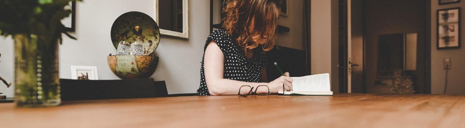 Junge Frau sitzt am Tisch und macht Notizen in einen Planer.