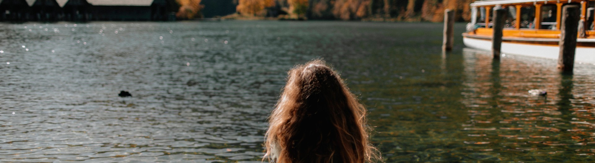 Junge Frau sitzt am Ufer eines Sees.