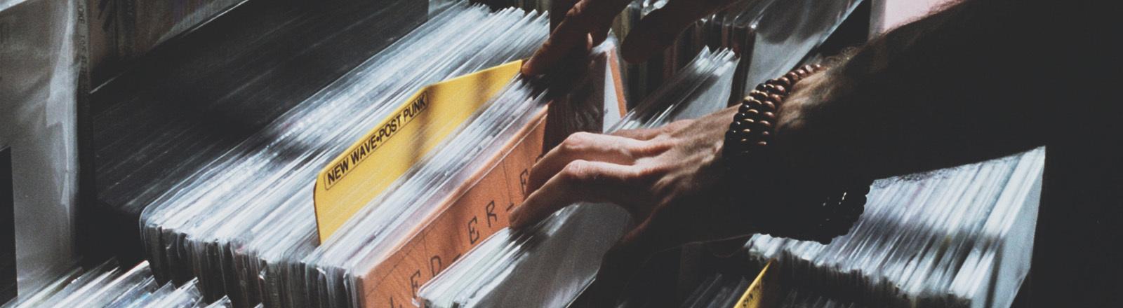 Eine Hand fährt durch eine Schallplattensammlung