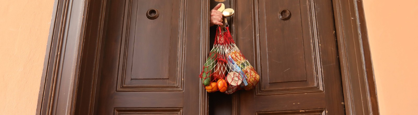 Einkäufe werden kontaktlos in eine Wohnung geholt.
