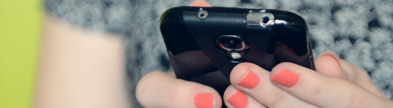 Hände mit lackierten Fingernägeln tippen auf einem Smartphone.