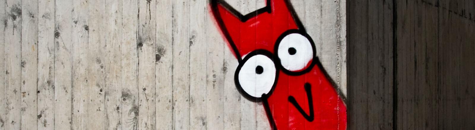 Ein Graffiti von einem kleinen roten Wesen, das um eine Gebäudeecke lugt