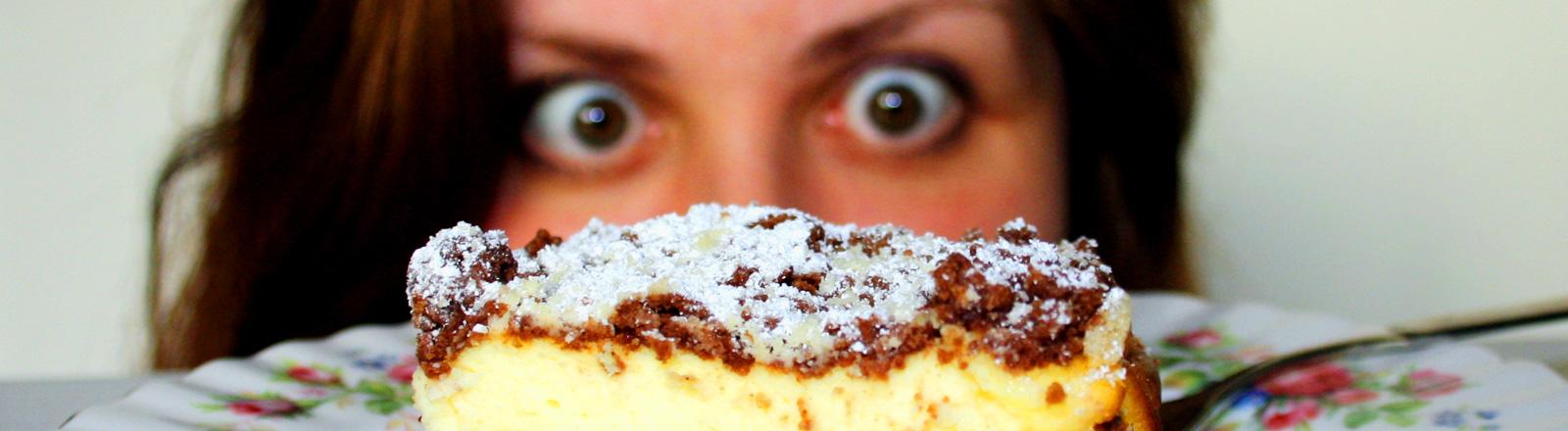 Frau starrt hungrig auf Kuchenstück